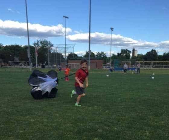 Youth soccer player running with a parachute - for speed training.